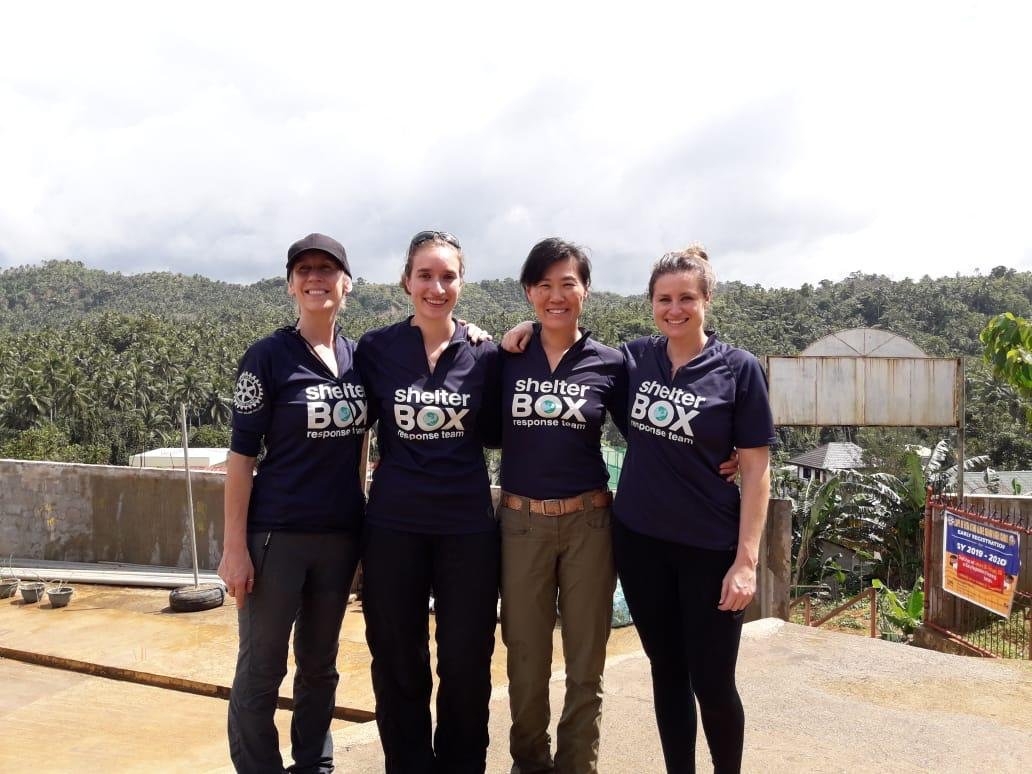 four women in ShelterBox team shirts stand in front of a mountainous landscape.