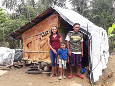 A family of three stands outside a straw hut covered by a white tarpaulin. They are a man, a woman, and a child. Two solar lanterns hang from the hut.